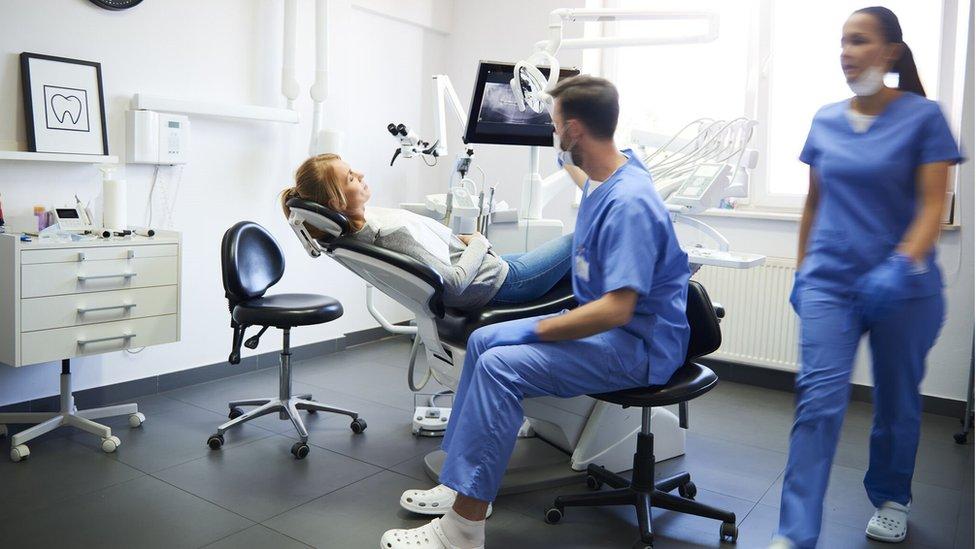 A dentist and dental nurse attend a patient