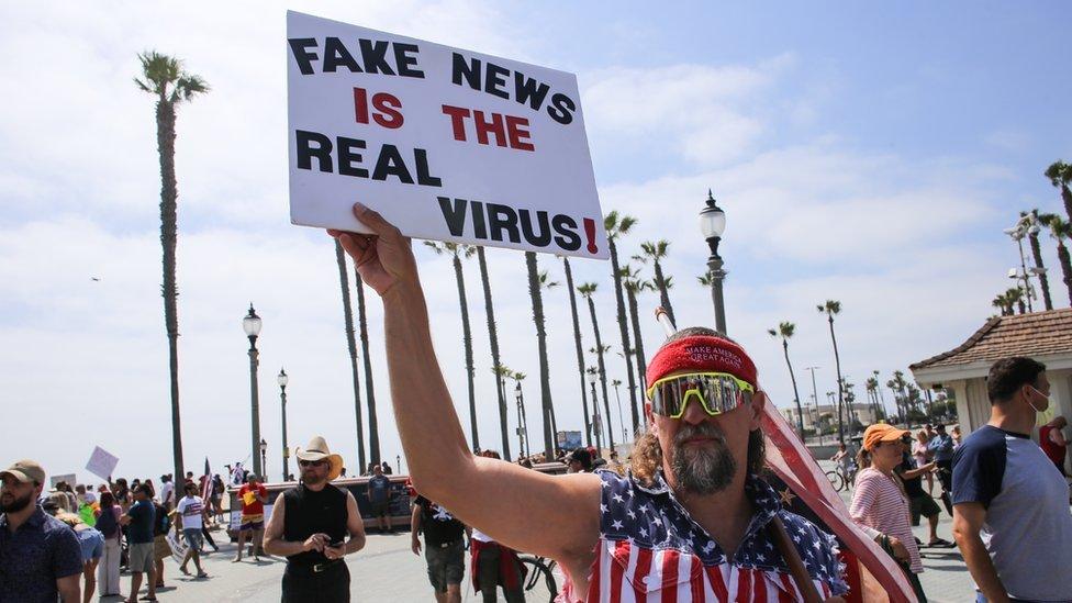 Transparent demonstranta izražava sumnju u postojanje korona virusa tokom protesta u Kaliforniji s početka maja