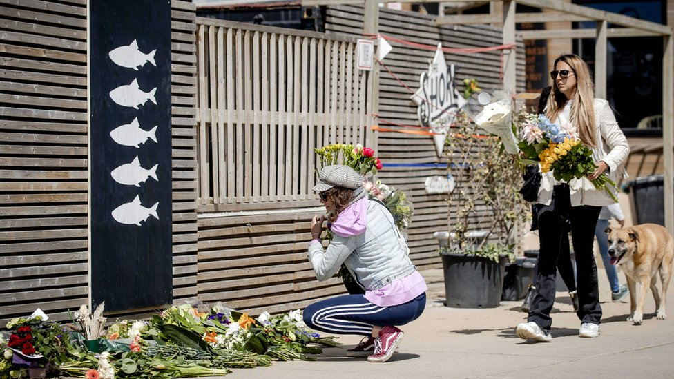 People lay flowers at surf club The Shore in Scheveningen, The Netherlands, 12 April 2020