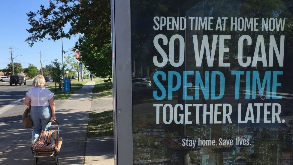 A street display shows a social distancing message in the Canadian city of Toronto