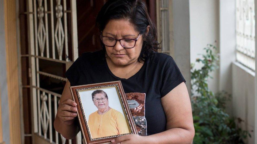 Elsa Maldonado holding a portrait of her mother