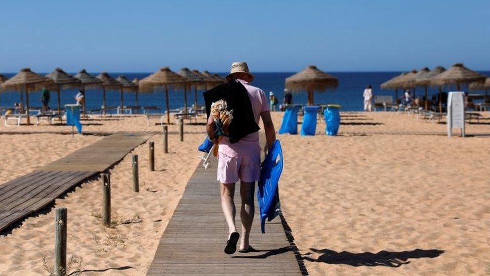A man arrives at Vilamoura beach amid the coronavirus disease (COVID-19) pandemic, in Quarteira