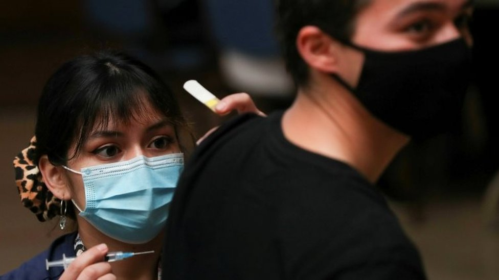 A healthcare worker prepares to vaccinate a man in Santiago, Chile. File photo