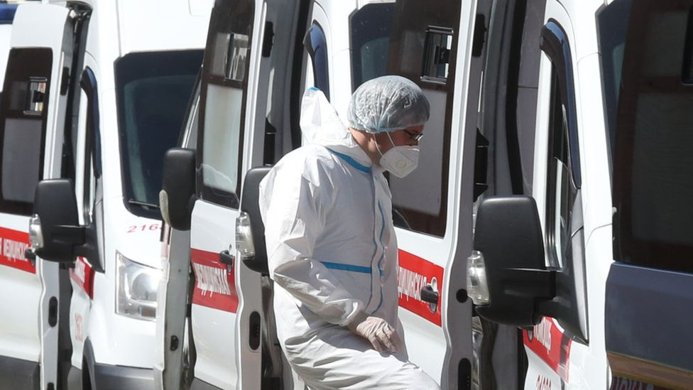 A medical worker enters an ambulance parked outside admissions at Pokrovskaya Municipal Hospital, St Petersburg
