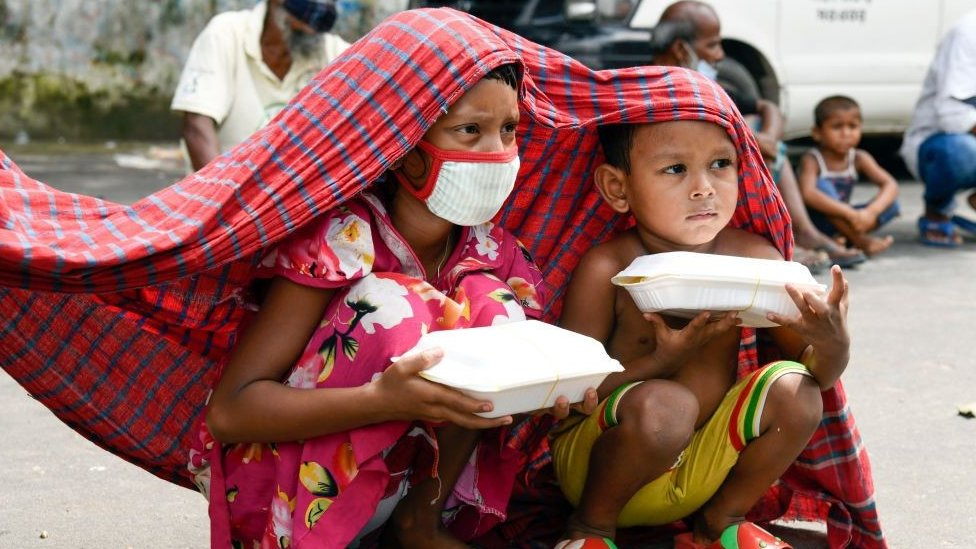 Two Bangladeshi children hold food parcels given away during the country's most recent lockdown