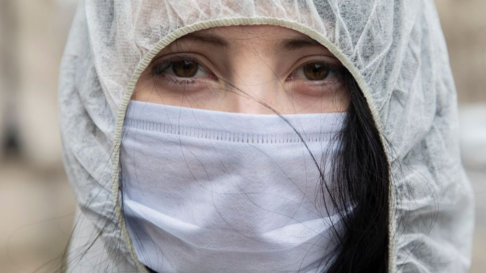 A young woman wearing protective gear and a face mask